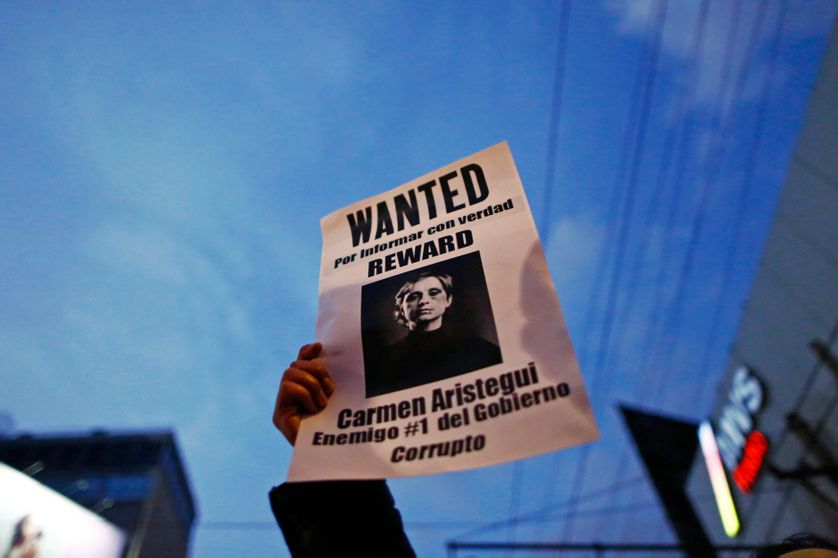 A demonstrator holds a sign during a protest against the dismissal of two investigative journalists from a news programme on MVS