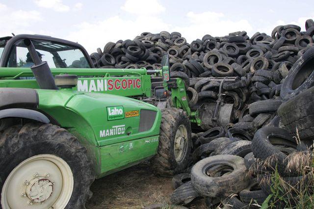 Des pneux abandonnés dans une décharge, ramassés pour être recyclés