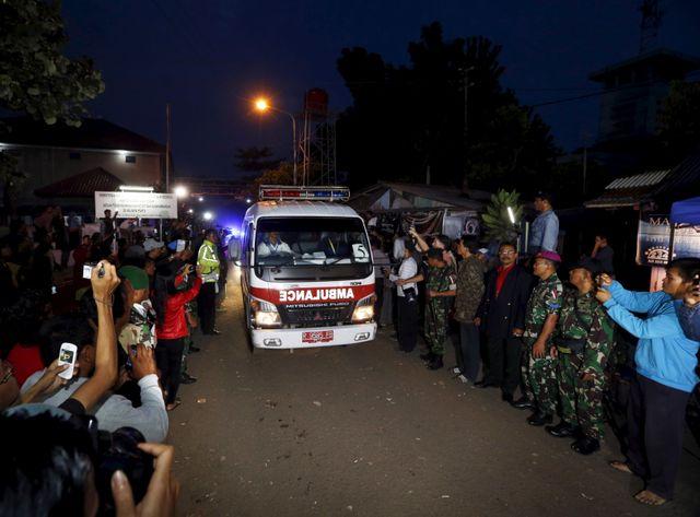 Une ambulance transportant le cercueil d'un des huit fusillés quitte l'île où ils ont été passés par les armes