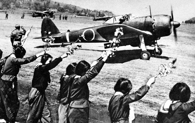 Lycéennes japonaises saluant Toshio Anazawa, un pilote kamikaze, avec des banches de cerisiers en fleurs le 12 avril 1945