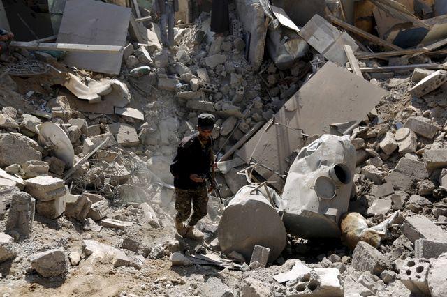 Un soldat marche près du cratère causée par une attaque aérienne près de l'aéroport de Sanaa