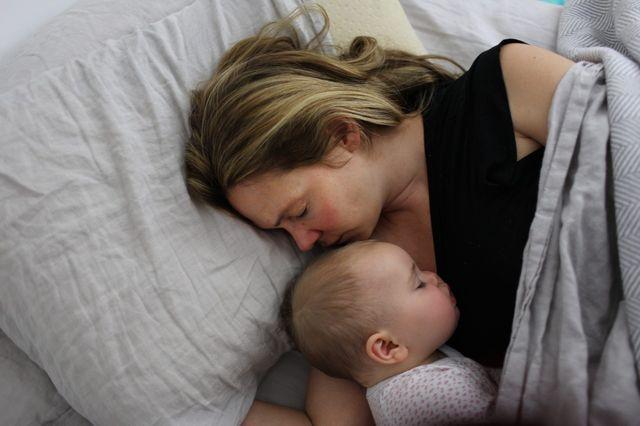 Une mère dormant avec son enfant.