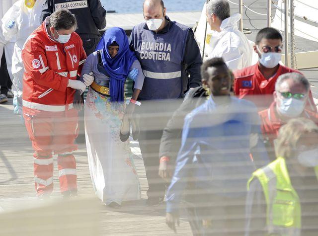 Une migrante est aidée à débarquer d'un bateau de la Garde côtière dans le port de Palerme