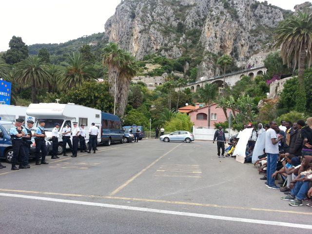 Une centaine de migrants face à des policiers français les empêchant de passer