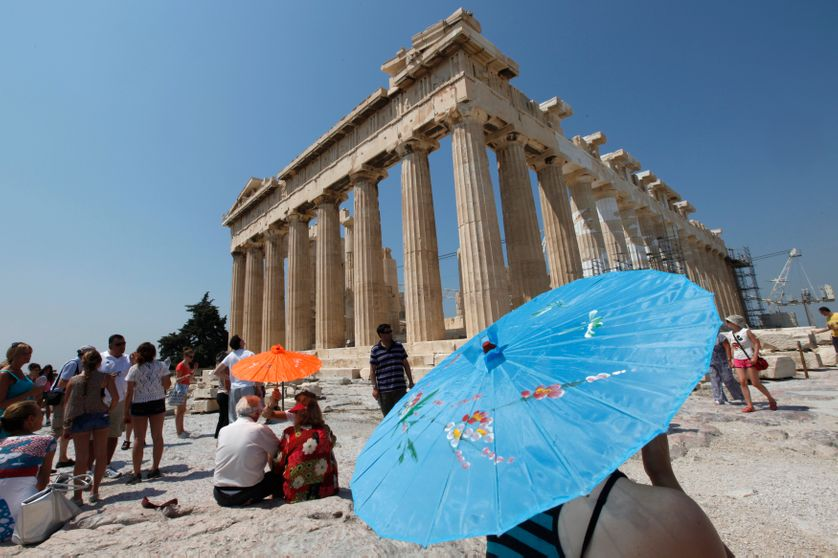 A woman protects herself from the sun under an umbrella at the top of the Acropolis.
