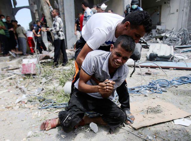 A Rafah un Palestinien pleure alors qu'on évacue le cadavre de sa mère des décombres de leur maison détruite par une frappe