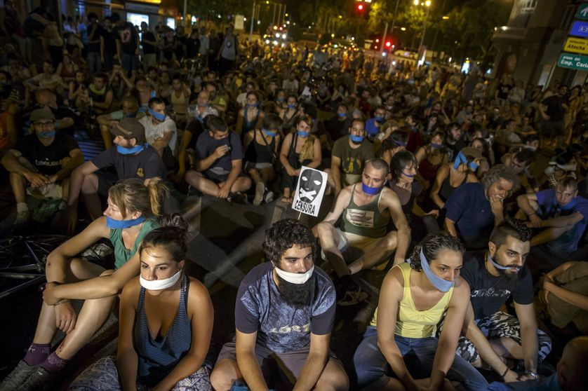 Demonstrators with their mouths taped sit outside the Spanish parliament during a protest against Spanish government's new secur
