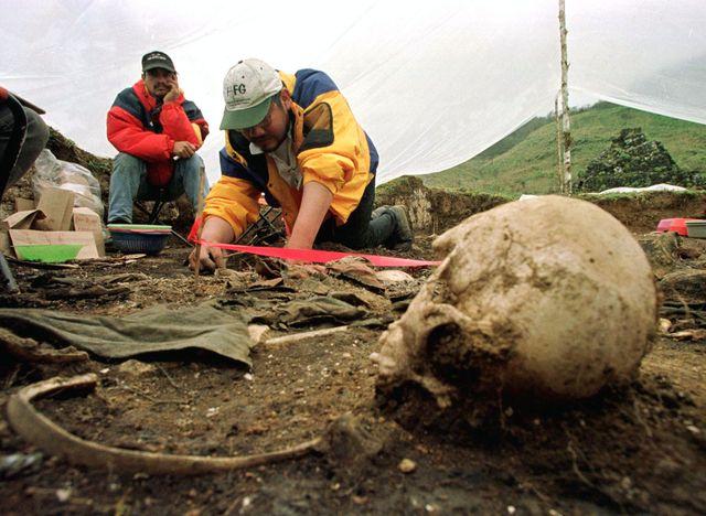 Un archéologue judiciaire guatémaltèque fouille autour des restes humains  déterrés sur le site d'un massacre commis 30 ans avan