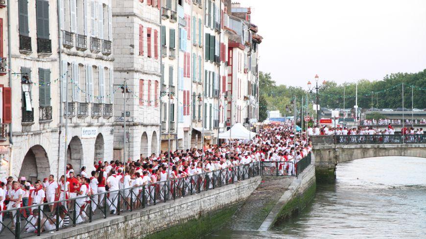 la foule des festayres sur les bords de la Nive lors des Fêtes de Bayonne