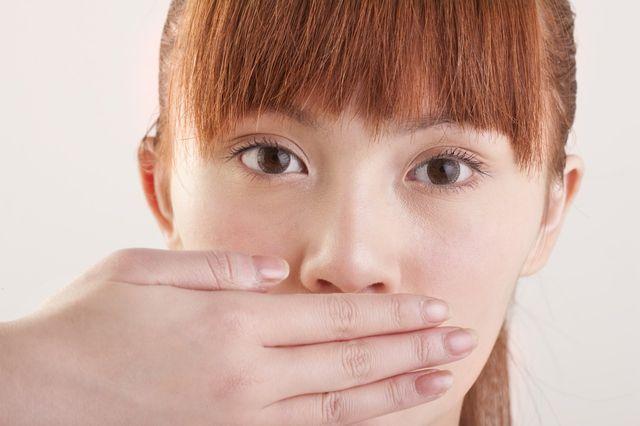 Jeune asiatique se couvrant la bouche avec la main