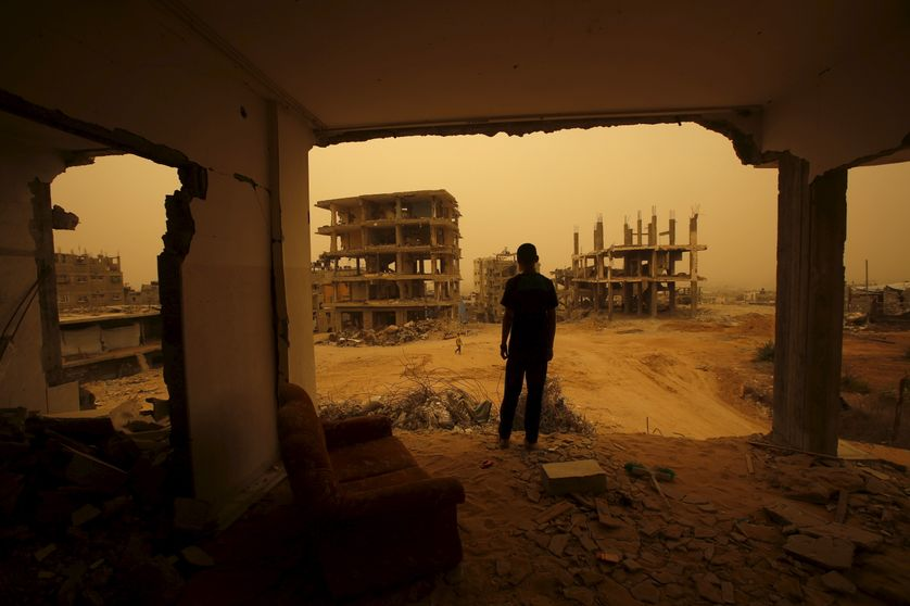 A Palestinian stands inside the remains of a house, during a sandstorm in Gaza.