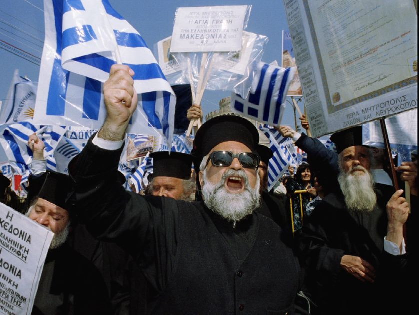 Greek Orthodox priests chant slogans and wave Greek flags as they take part in a demonstratio