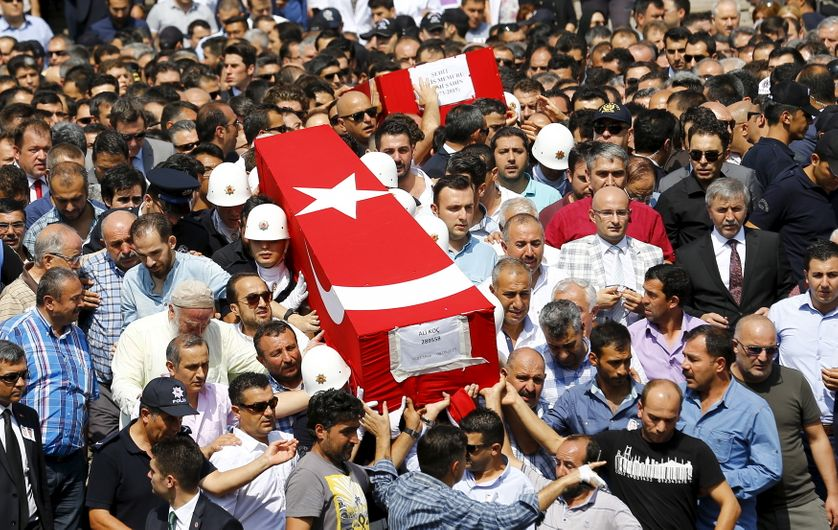 People carry the flag-draped coffins of police officers Fehmi Sahin and Ali Koc, two of the 14 police officers who were killed d