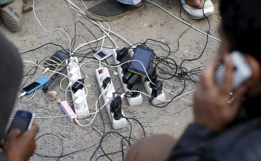 Des migrants rechargent leur portable à Calais