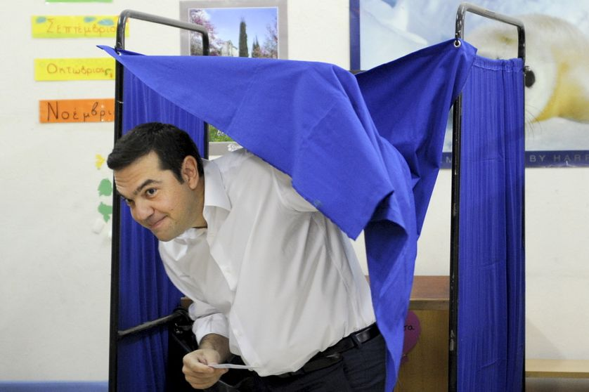 Former Greek prime minister and leader of leftist Syriza party Alexis Tsipras holds his ballot as he exits a voting booth during