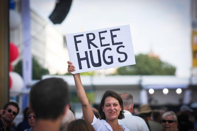 """Jeune femme proposant des """"free hugs"""" (câlins gratuits) dans la rue"""