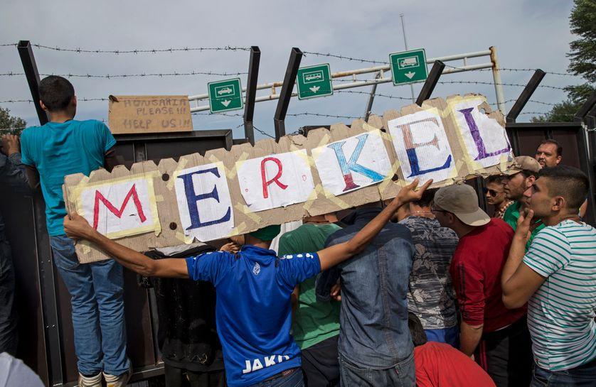 "Migrants hold a banner reading ""Merkel""."