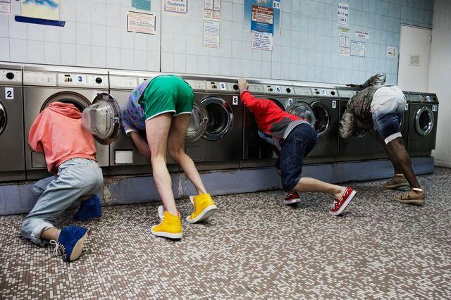 Quatre jeunes regardant dans des machines à laver