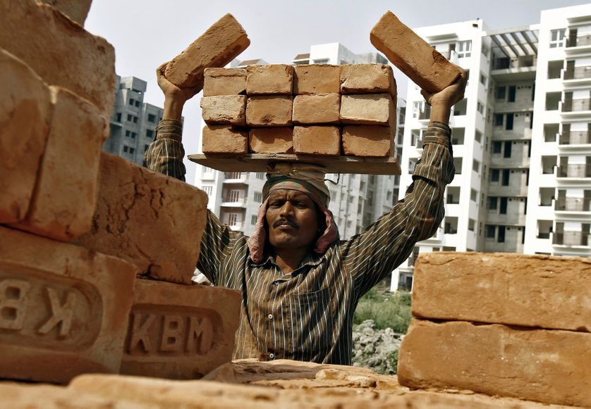 A labourer stacks bricks on his head at the construction site of a residential complex in Kolkata.