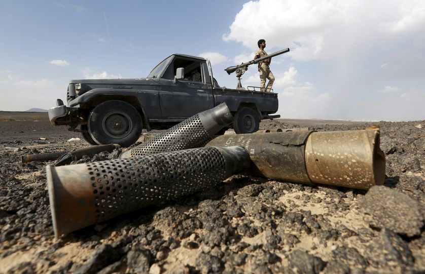 A fighter of the anti-Houthi Popular Resistance Committees stands on a truck during fighting with Houthi fighters near Yemen's n