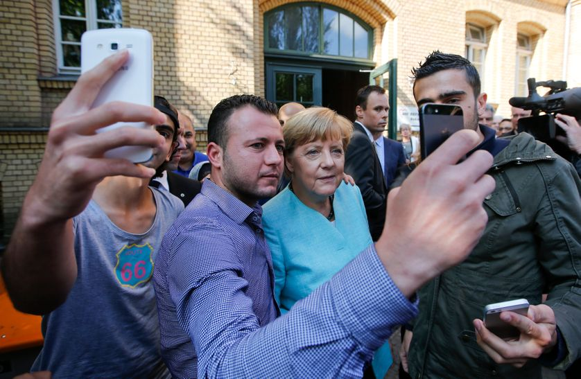 Migrants from Syria and Iraq take selfies with German Chancellor Merkel outside a refugee camp
