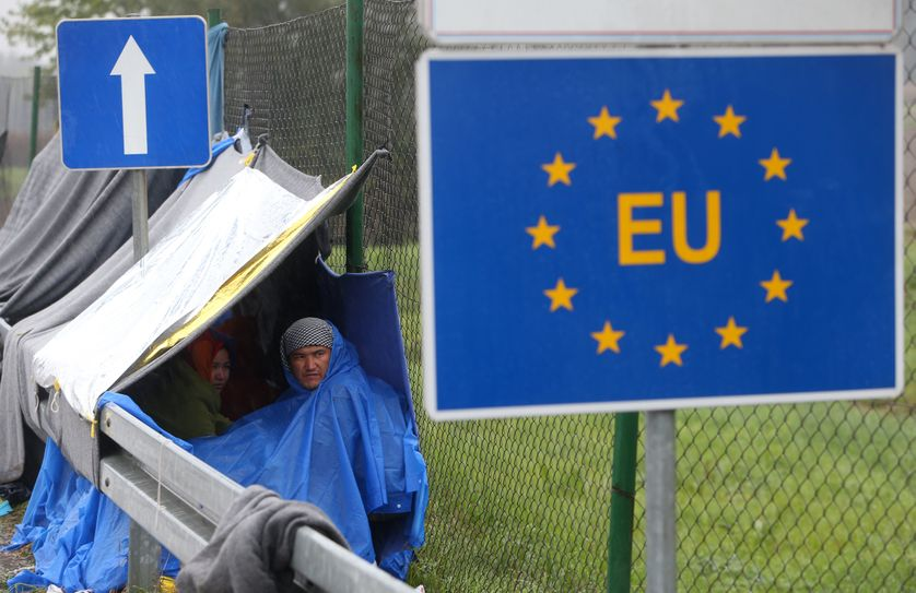 An EU sign is seen as migrants wait in the no man's land to cross the border to Slovenia.