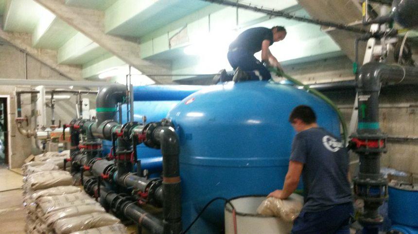 Après la réparation, les techniciens de la SAUR remplissent les filtres de sable