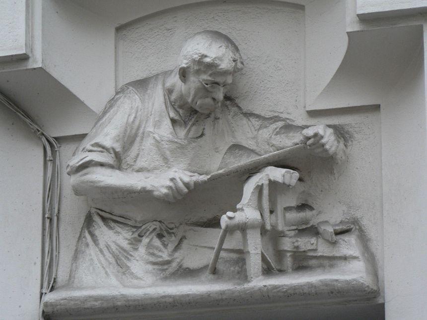 Un armurier sur son étau au fronton du 21 de la rue Henri Barbusse