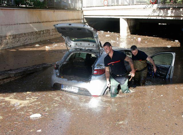 Des pompiers tentent de dégager un véhicule dans les rues inondées de Cannes