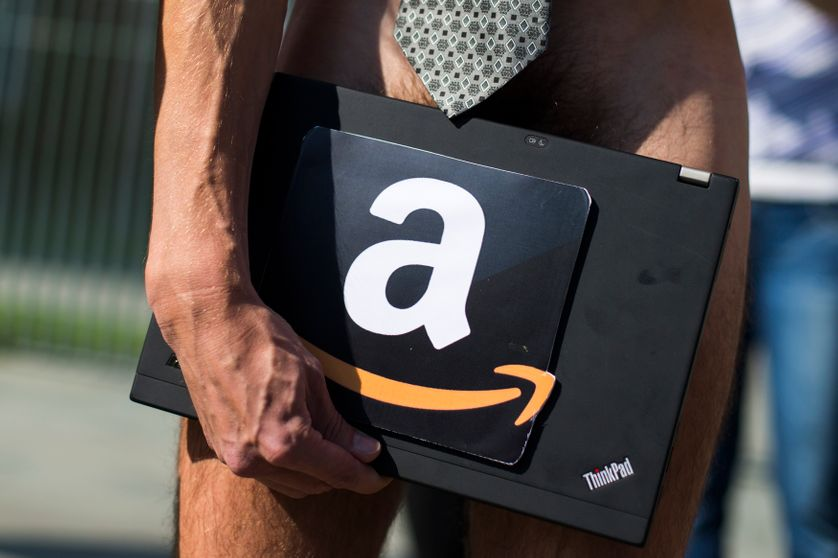 A man holds a laptop with the logo of the online retailer Amazon during a protest by the Attac pressure group outside the Chance