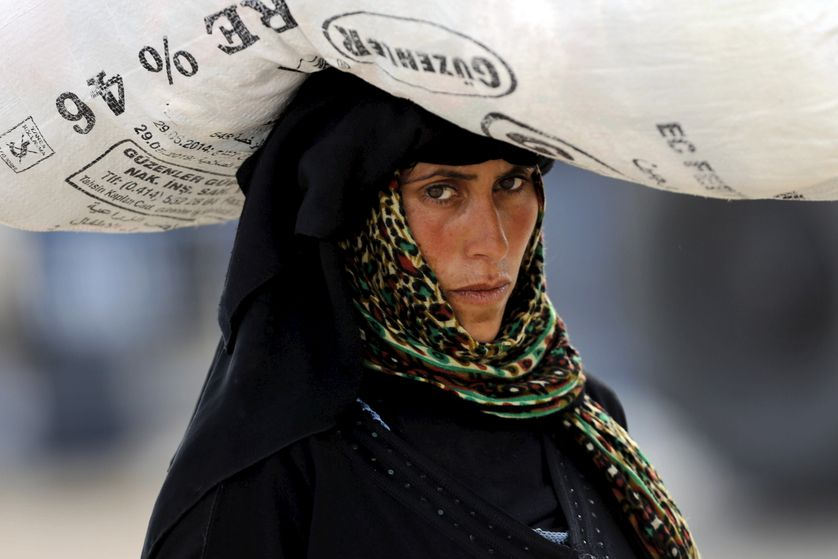A Syrian refugee woman carries her belongings as she crosses into Turkey at Akcakale border gate in Sanliurfa...
