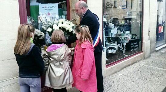 Dépôt de fleurs devant la pharmacie de la mère de la victime