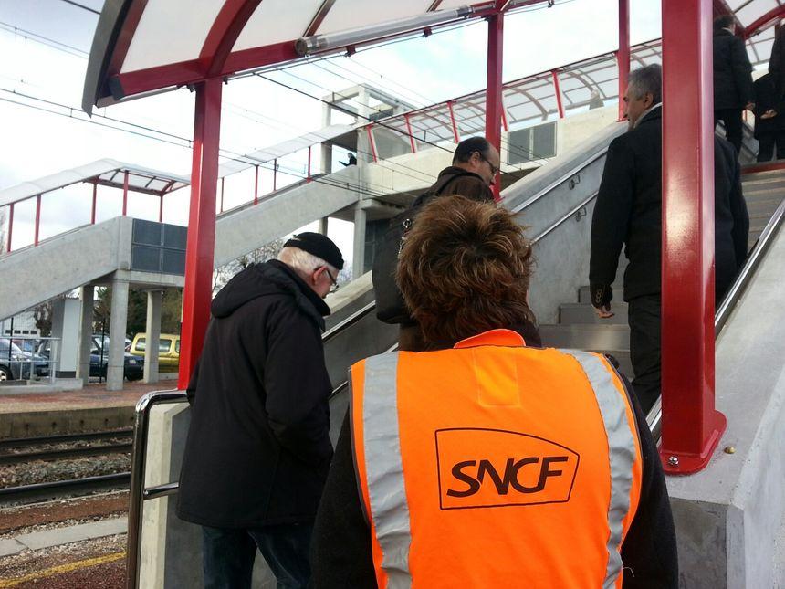 Un agent SNCF veille à ce que les usagers prennent bien la passerelle.
