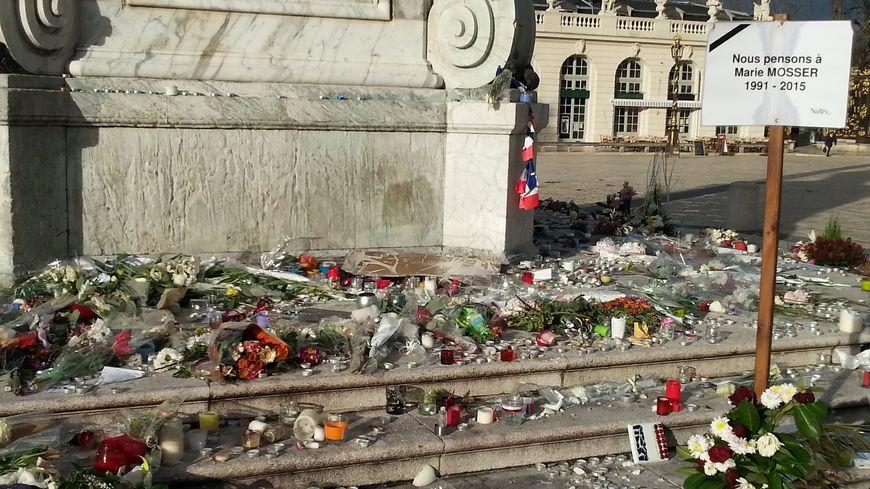Encore énormément de fleurs et de bougies au pied de la statue de Stanislas