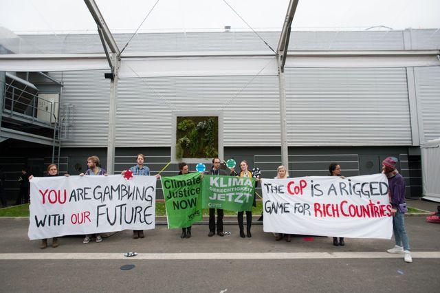 Des manifestants à l'intérieur de la COP21. Sur les panneaux, on lit : « Un jeu truqué pour les pays riches »