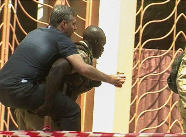 Un otage blessé est évacué par un policier malien