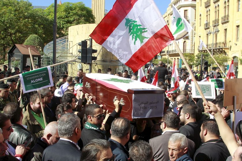 an empty coffin symbolizing the Constitution of Lebanon during a protest near the parliament building, where lawmakers are meeti