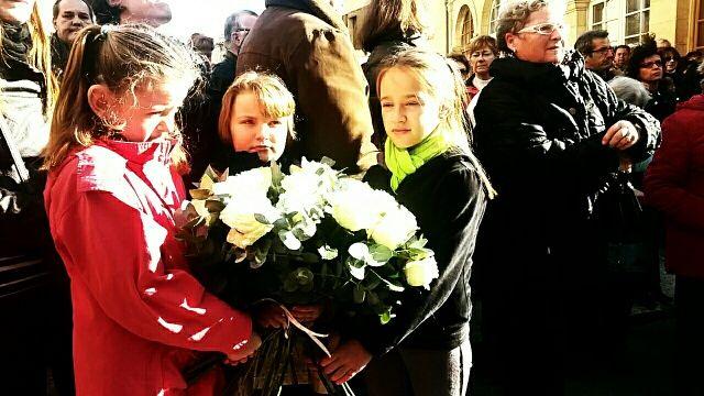 Trois jeunes filles tiennent un bouquet de roses blanches en hommage à Maxime