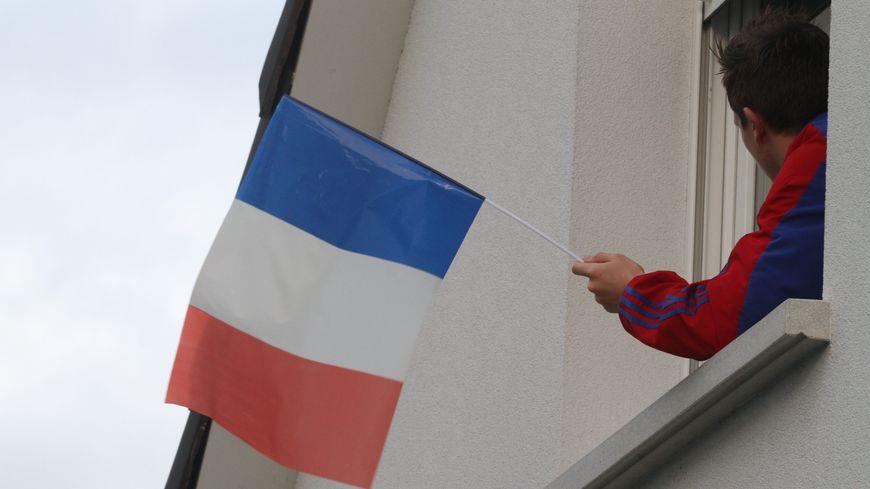 Un homme accroche un drapeau tricolore à sa fenêtre, en hommage aux victimes