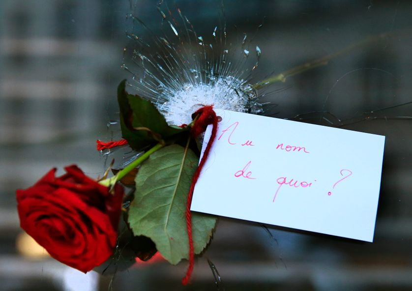 A rose placed in a bullet hole in a restaurant window the day after a series of deadly attacks in Paris.