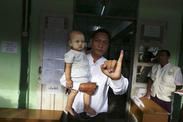 Un birman montre la preuve de son vote sur son doigt