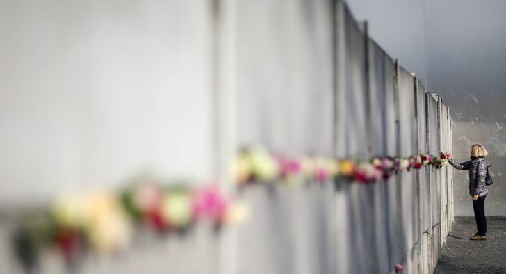 Une femme place une rose dans le memorial du mur de Berlin, 26 ans après sa chute