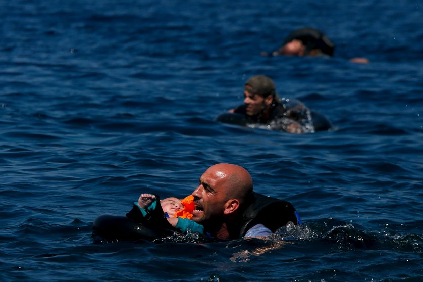 A Syrian refugee holding a baby in a lifetube swims towards the shore after their dinghy deflated some...