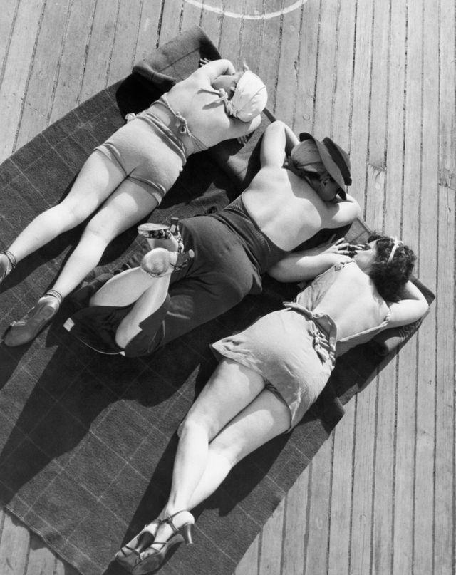 Trois baigneurs sur une serviette sur le pont du navire (ca. 1930 - 1959)