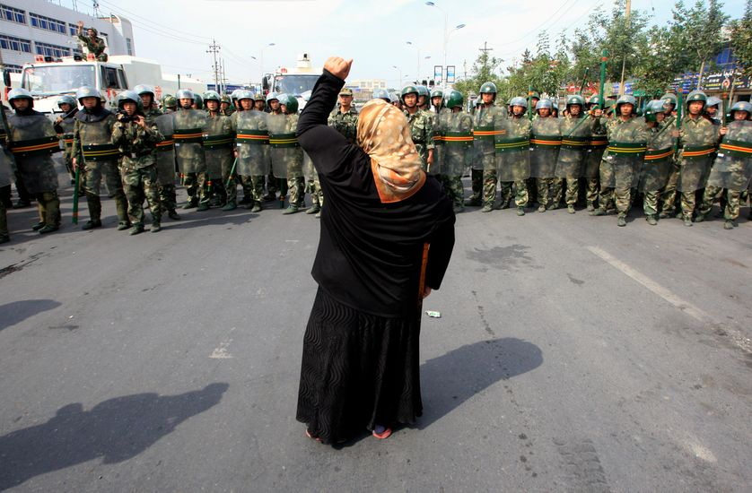 Chinese paramilitary police wearing riot gear as a crowd of angry locals confront security forces on a street in the city of Uru