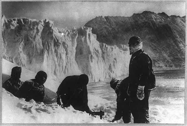 Un trou est creusé dans l'iceberg, à l'aide d'une herminette.