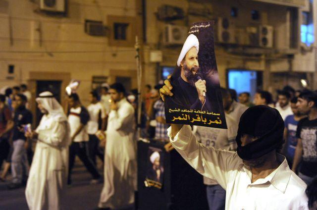 Un manifestant brandit une photo de Cheikh al-Nimr lors d'un rassemblement à Qatif, contre son arrestationl'arresta