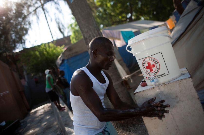 A Haïti, un homme se lave les mains grâce à une solution de la Croix Rouge