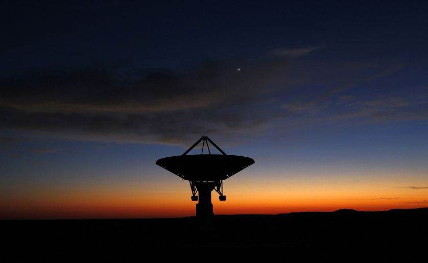 Dawn breaks over a radio telescope dish of the KAT-7 Array pointing skyward