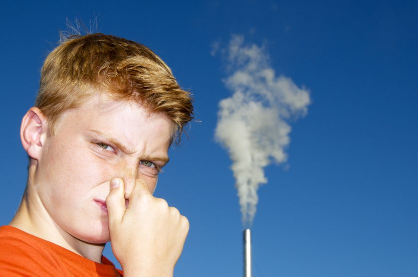 Enfant qui se bouche le nez à cause de mauvaises odeurs industrielles